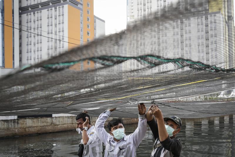 В Джакарте стыдливо прикрыли сеткой грязную реку
