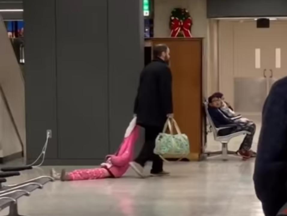 Отец протащил непослушную дочь за капюшон по аэропорту (видео)