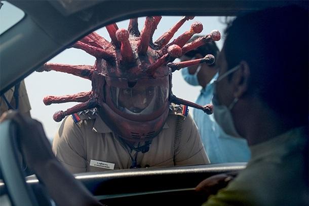 Индийский полицейский носит шлем в форме коронавируса