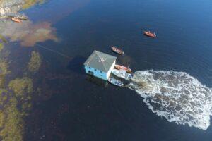 Канадцы перевезли на лодках вековой дом на другой берег залива
